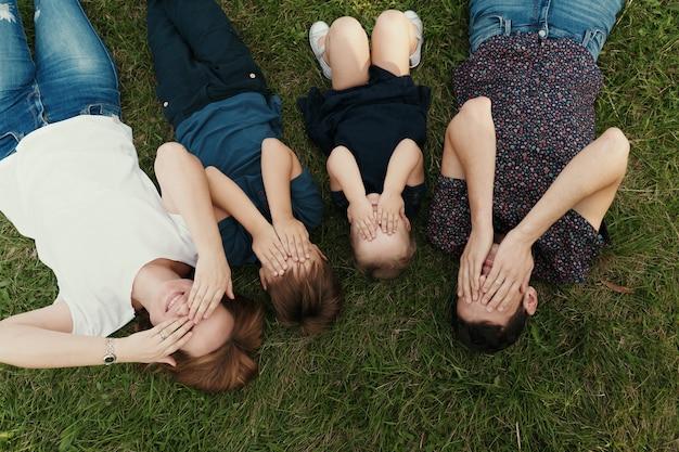 Porträtfamilie mit kindern, die auf dem gras liegen Kostenlose Fotos