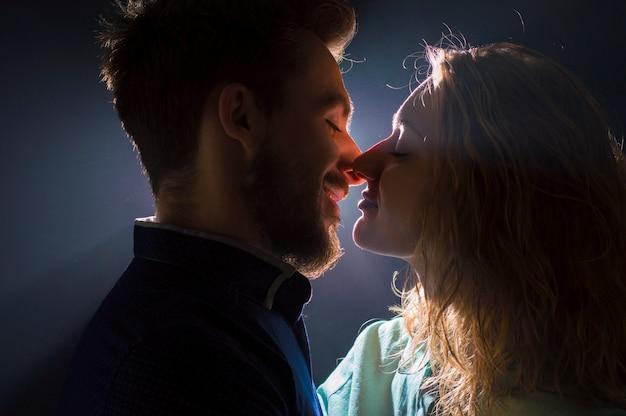 Porträtfoto eines sexy jungen paares im vorkuss in den lichtströmen Premium Fotos