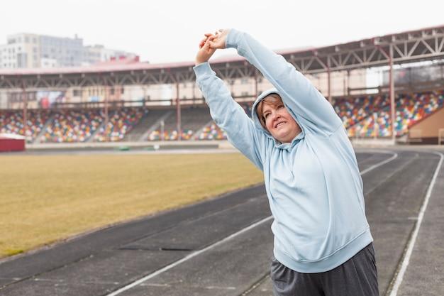 Porträtfrau am stadion, das sich ausdehnt Kostenlose Fotos