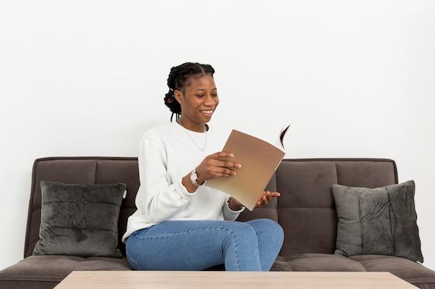 Porträtfrau auf couch mit buch Kostenlose Fotos