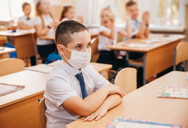 Porträtkind mit gesichtsmaske während des coronavirus in der schule Premium Fotos