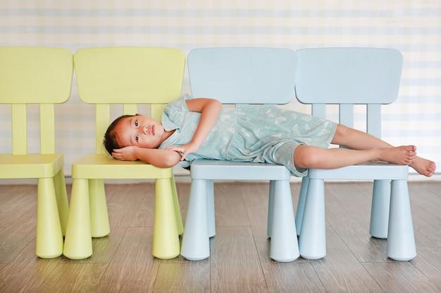 Porträtkindervorschulmädchen in einem kindergartenraum, der auf plastikbabystuhl liegt. Premium Fotos