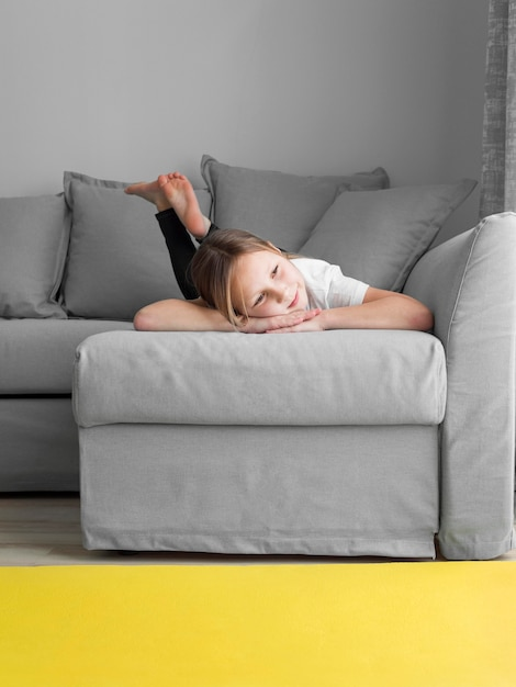 Porträtmädchen zu hause auf der couch Kostenlose Fotos