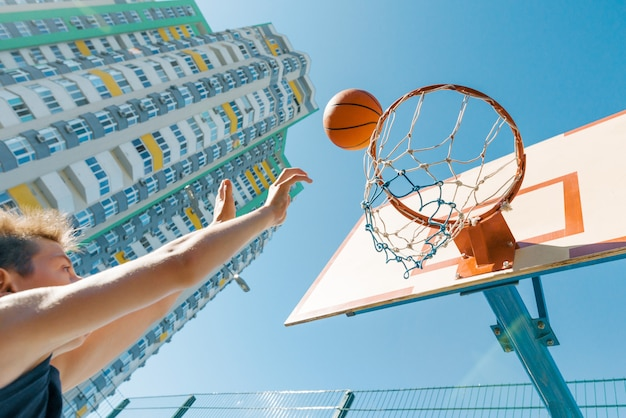 Porträtstraßen-basketball-spieler im freien, der mit dem ball am sonnigen tag spielt. Premium Fotos