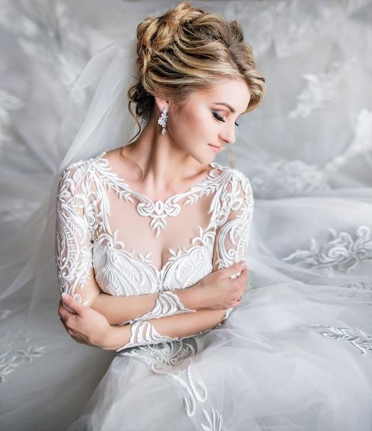 Portrair der träumerischen blonden braut, die in einem luxuxraum vor der zeremonie aufwirft Kostenlose Fotos