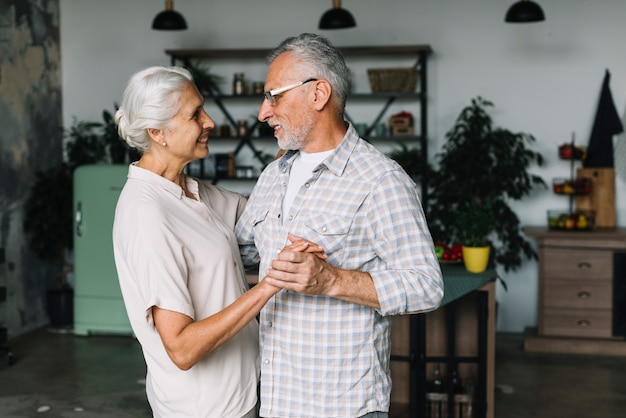 Portrait der älteren paare, die zusammen in küche tanzen Kostenlose Fotos
