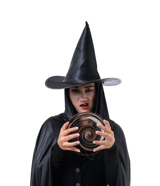 Portrait der frau im schwarzen furchtsamen hexe halloween-kostüm, das mit hut steht Premium Fotos