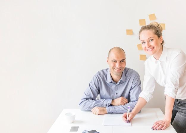 Portrait der geschäftsfrau und des geschäftsmannes, die im büro arbeiten Kostenlose Fotos