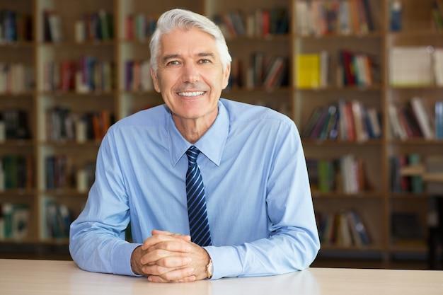 Portrait der lächelnden älteren geschäftsmann auf bibliothek Kostenlose Fotos