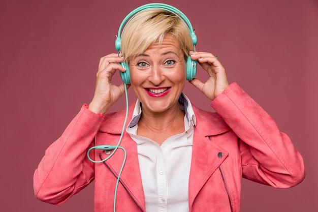 Portrait der mittleren gealterten frau mit kopfhörern Kostenlose Fotos