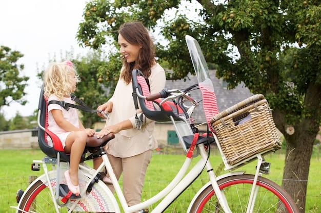 Portrait der mutter und der tochter mit fahrrad im park Premium Fotos