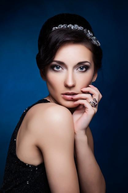 Portrait der schönen brunettefrau im schwarzen kleid. kosmetische lidschatten. Premium Fotos