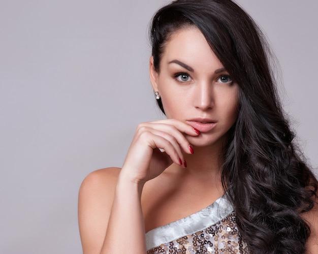 Portrait der schönen frau mit gelockter frisur und hellem make-up Premium Fotos