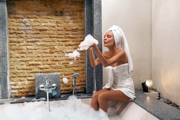 Portrait der schönen frau mit tuch auf ihrem kopf und schlagschaum beim nehmen des bades Premium Fotos