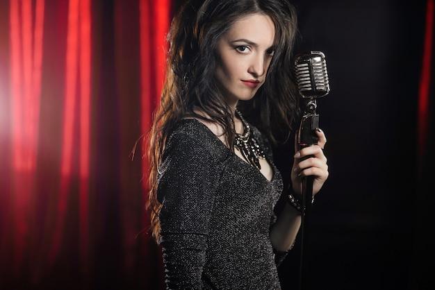 Portrait der schönen frau singend im mikrofon Premium Fotos