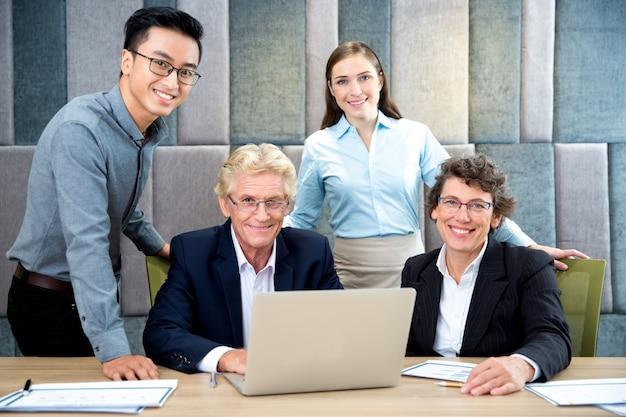 Portrait des erfolgreichen Team an Laptop im Büro Kostenlose Fotos