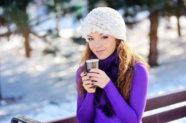 Portrait des schönen mädchens, das heißes getränk im schneebedeckten winter trinkt. Premium Fotos