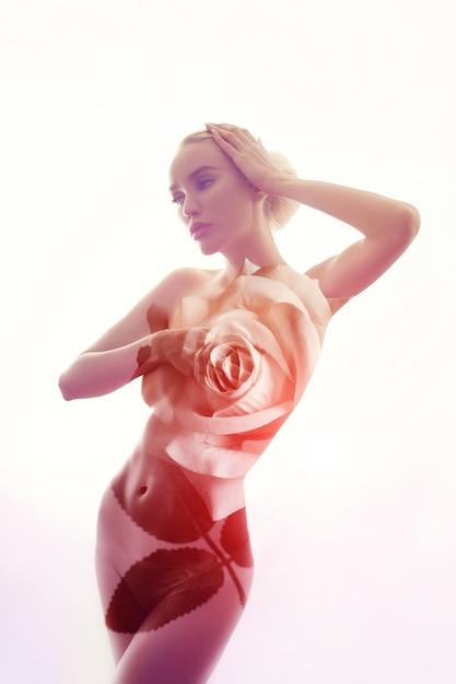 Portrait einer blanken frau mit doppelbelichtung der rosafarbenen blumen. art nude frau mit perfekter figur Premium Fotos