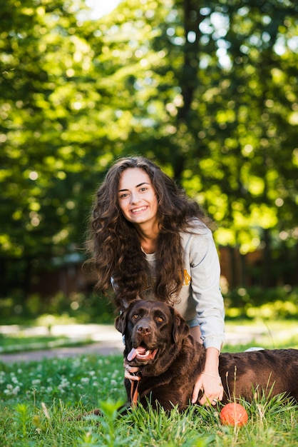 Portrait einer glücklichen jungen frau und ihres hundes im garten Kostenlose Fotos