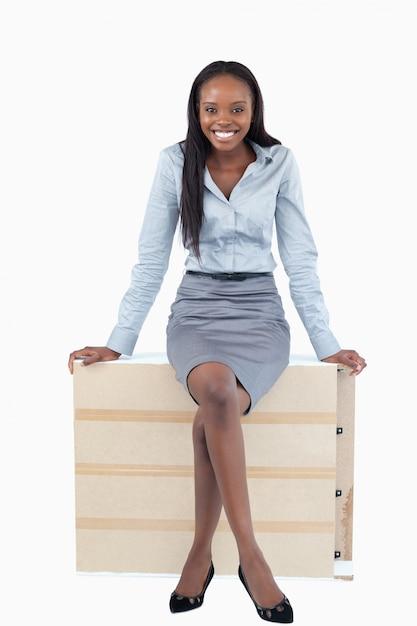 Portrait einer lächelnden geschäftsfrau, die auf einer platte sitzt Premium Fotos