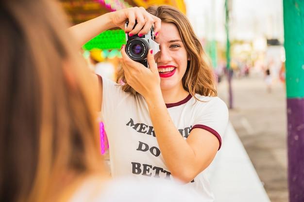 Portrait einer lächelnden jungen frau, die foto ihres freundes macht Kostenlose Fotos