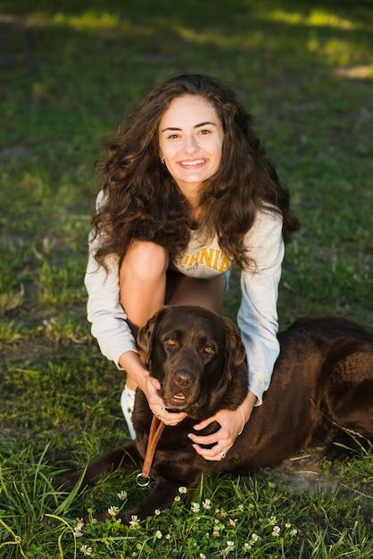Portrait einer lächelnden jungen frau mit ihrem hund im