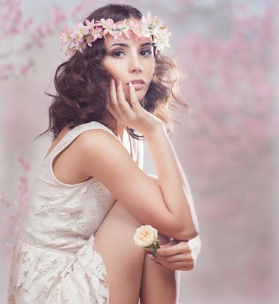 Portrait einer schönen frau mit blumen in ihrem haar. Premium Fotos