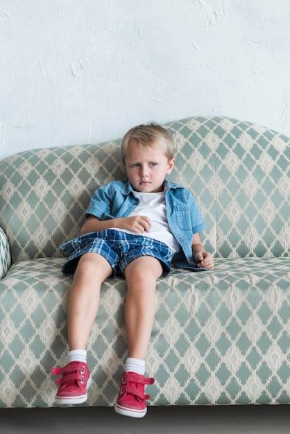 Portrait eines blonden gebohrten jungen, der auf sofa sitzt Premium Fotos