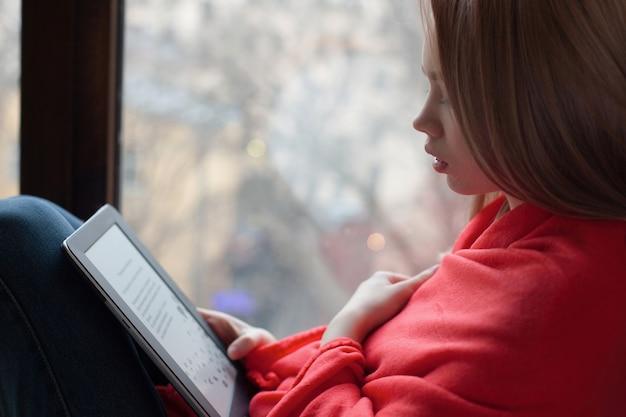 Portrait eines jungen mädchens, das ein ebook liest. Premium Fotos
