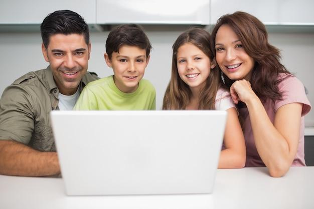 Portrait eines lächelnden paares mit den kindern, die laptop verwenden Premium Fotos