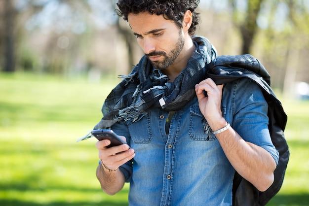 Portrait eines mannes, der seinen handy in einem park verwendet Premium Fotos