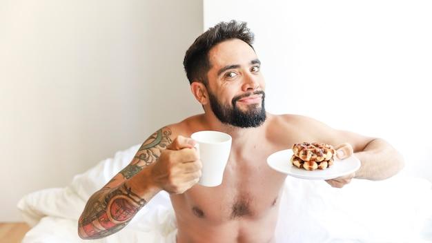 Portrait eines mannes mit tasse kaffee und waffel auf platte Kostenlose Fotos