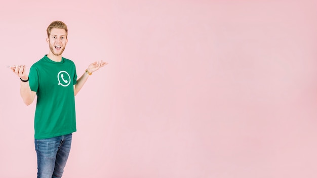 Portrait eines überraschten mannes mit smartphone auf rosafarbenem hintergrund Kostenlose Fotos