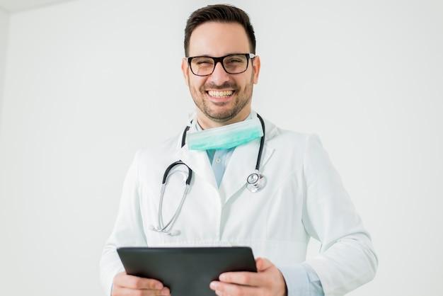 Portrait von doktor mit der tablette getrennt auf weiß Premium Fotos