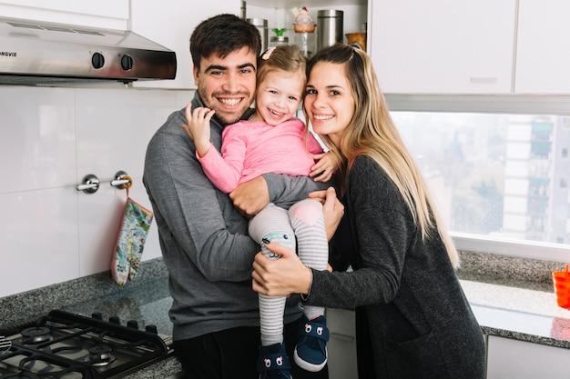 Portrait von glückliche eltern mit ihrer tochter in der küche Kostenlose Fotos