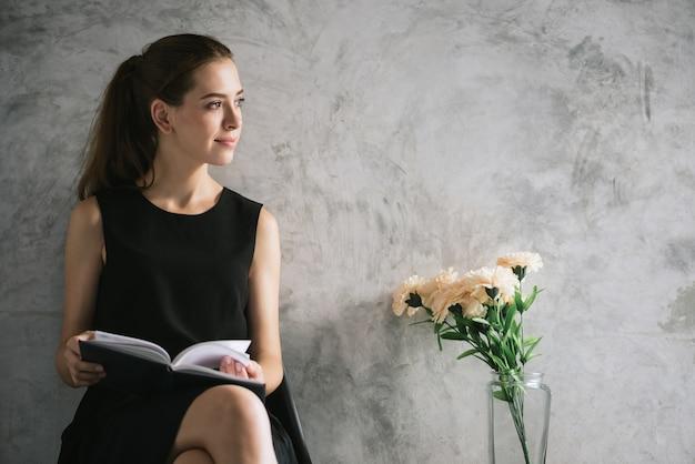 Porträt eines schönen Buches der jungen Frau Lese, das im Wohnzimmer sich entspannt. Vintage Effekt Stil Bilder. Kostenlose Fotos