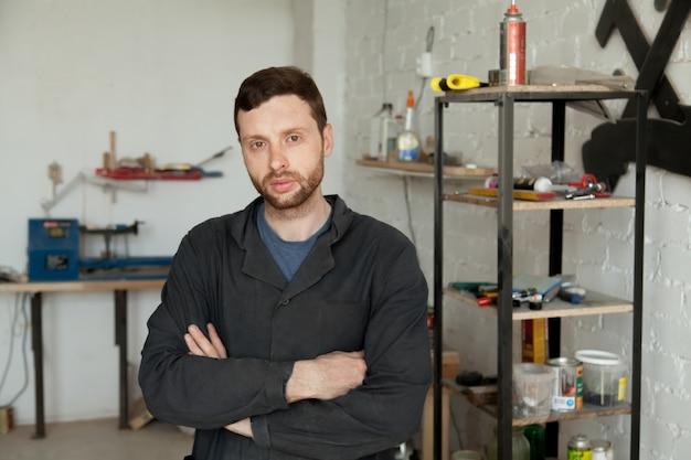 Porträt von ernster junger Heimwerker steht in eigener Werkstatt Innenraum Kostenlose Fotos