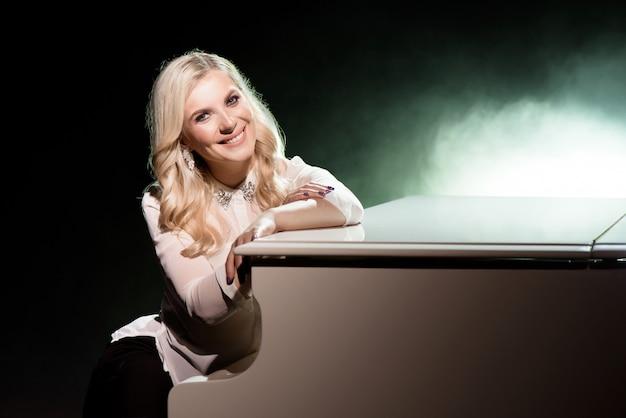 Portret des pianisten, der in der nähe des weißen klaviers auf der bühne im lichtstrahl aufwirft. Premium Fotos