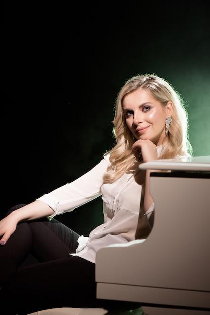 Portret des pianisten, der nahe weißes klavier auf der bühne im lichtstrahl aufwirft. Premium Fotos