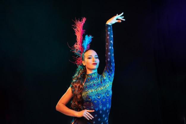 Posieren. schöne junge frau im karneval, stilvolles maskeradenkostüm mit federn auf schwarzer wand im neonlicht. copyspace für anzeige. feiertagsfeier, tanz, mode. festliche zeit, party. Kostenlose Fotos