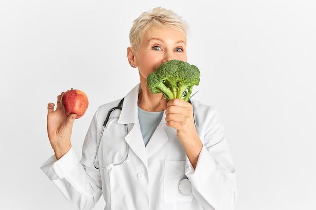 Positive ärztin mittleren alters mit apfel und brokkoli, die eine pflanzliche ernährung empfiehlt. lustige ärztin, die vorschlägt, gemüse zu essen, das lebenswichtige nährstoffe liefert, fettarm und kalorienarm Kostenlose Fotos