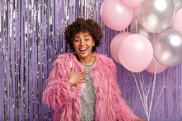 Positive afroamerikanerin kommt, um freund zum jubiläum zu gratulieren, hält luftballons, hält hand auf brust Kostenlose Fotos