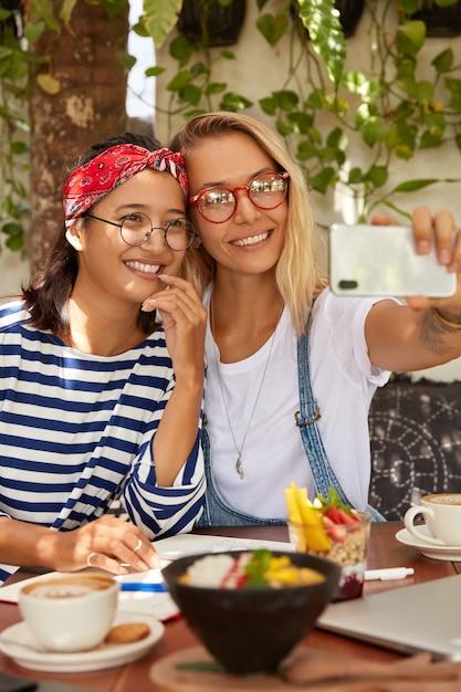 Positive blonde frau hält smartphone in händen, macht selfie-foto zusammen mit asiatischen freund, genießen sommerferien zusammen Kostenlose Fotos
