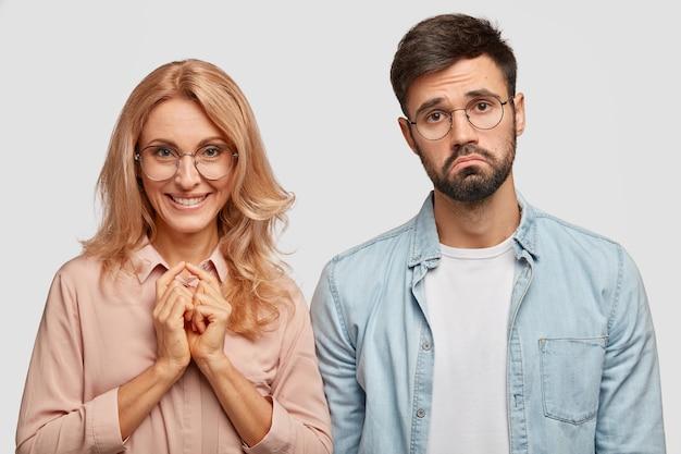 Positive blonde frau in brille hält hände zusammen, lächelt positiv, steht in der nähe seines jungen mannes Kostenlose Fotos