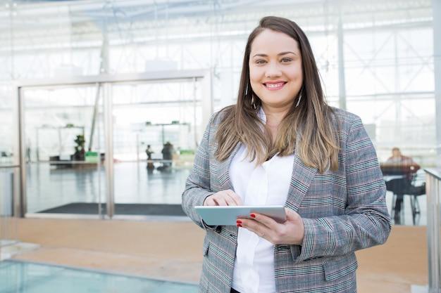 Positive dame mit der tablette, die im geschäftszentrum aufwirft Kostenlose Fotos