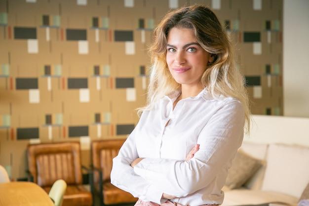 Positive erfolgreiche geschäftsfrau, die mit verschränkten armen im innenraum der zusammenarbeit oder des coffeeshops aufwirft, kamera betrachtet und lächelt Kostenlose Fotos
