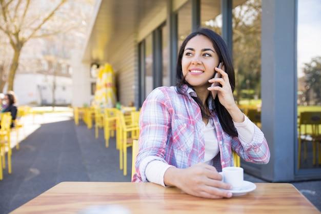 Positive frau, die am telefon spricht und kaffee trinkt Kostenlose Fotos