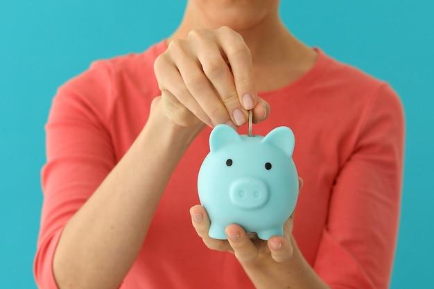 Positive frau, die münze in sparschwein einsetzt, planungsbudget, finanzielle einsparungen Premium Fotos