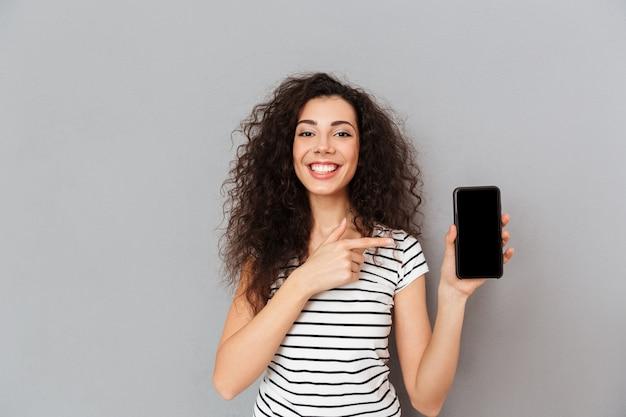 Positive frau mit kaukasischem auftritt zeigefinger zeigend mögen ihren smartphone annoncieren, der gegen graue wand aufwirft Kostenlose Fotos