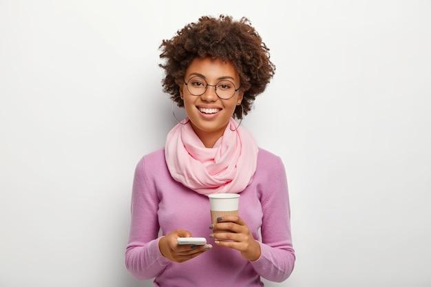 Positive gut aussehende erwachsene frau mit lockigem haar, trägt eine optische brille, violette kleidung, lädt mit dem smartphone etwas aus dem internet hoch und trinkt ein aromatisches heißes getränk aus einem pappbecher Kostenlose Fotos